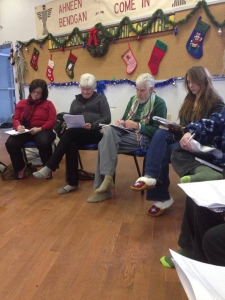 Group of older people on chairs writing away, Christmas decorations hang of the wall of the hall, behind them