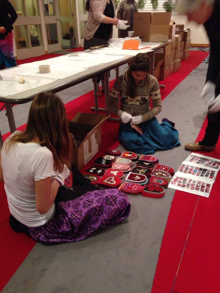 two young girls sit on floor unpacking the vamps with white gloves on their hands