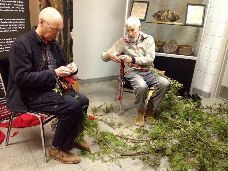 older man sitting with pile of cedar boughs in front of them that they are working with