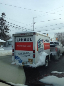 the back of a U-Haul trailer packed up and ready to leave on snowy day