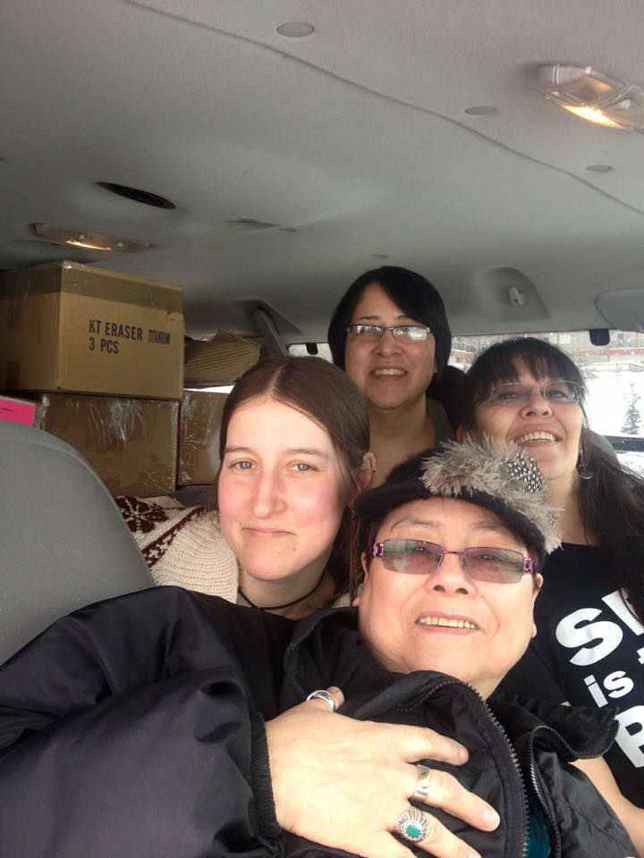 The heads of 4 women smiling at the camera while in a vehicle piled to ceiling with boxes