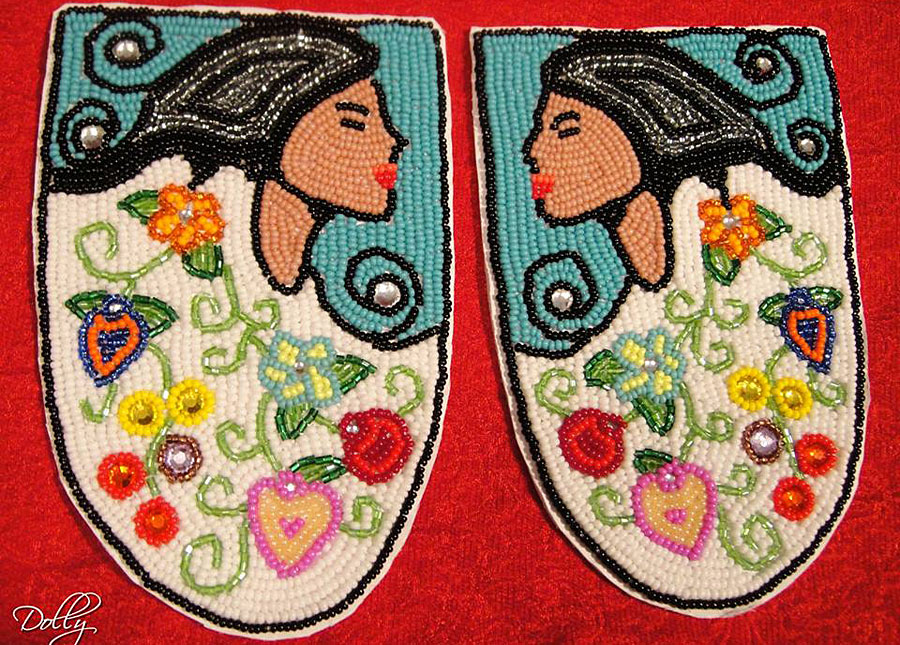 The tops of moccassins with beaded image of woman with long hair on either side, flowers aroud the bottom