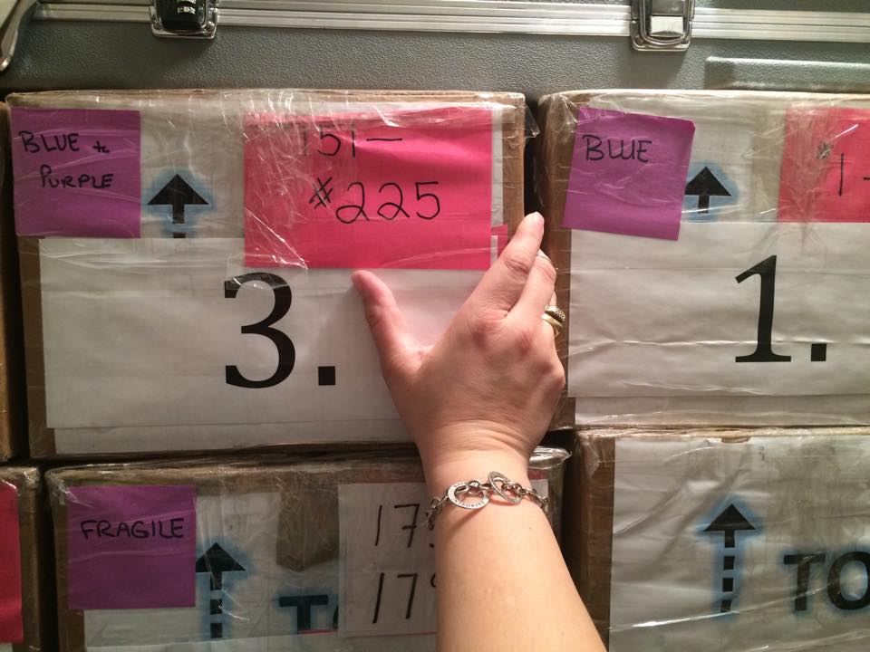 Woman's hand reaching out to touch cardboard boxes with labels