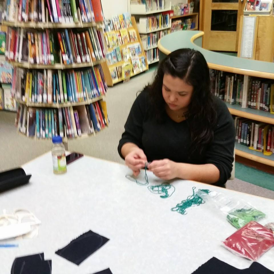 teenaged girl at library table sewing