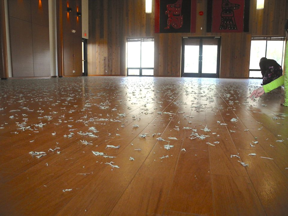 Wood floor scattered with pieces of dried sage