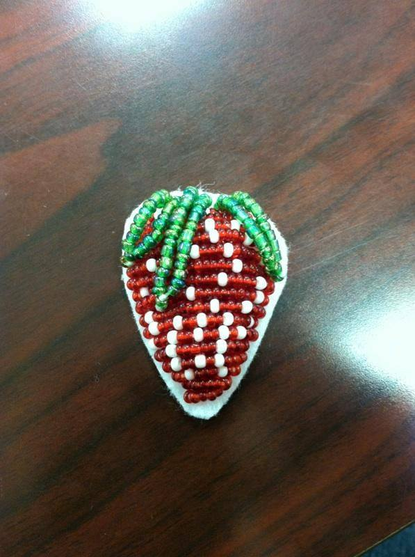 Close up of a completed beaded strawberry on table