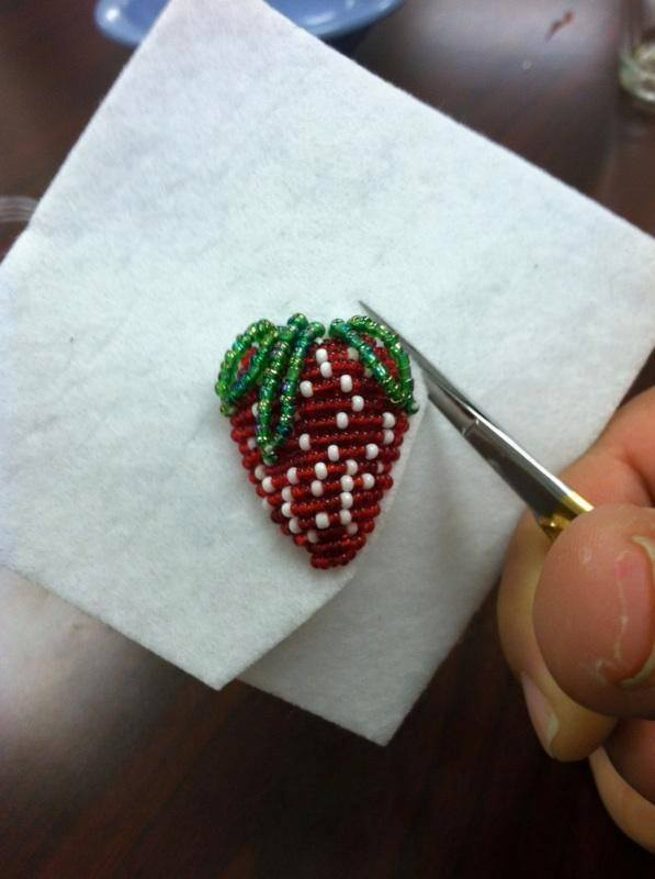 Cutting out the completed beaded strawberry from the fabric it is on