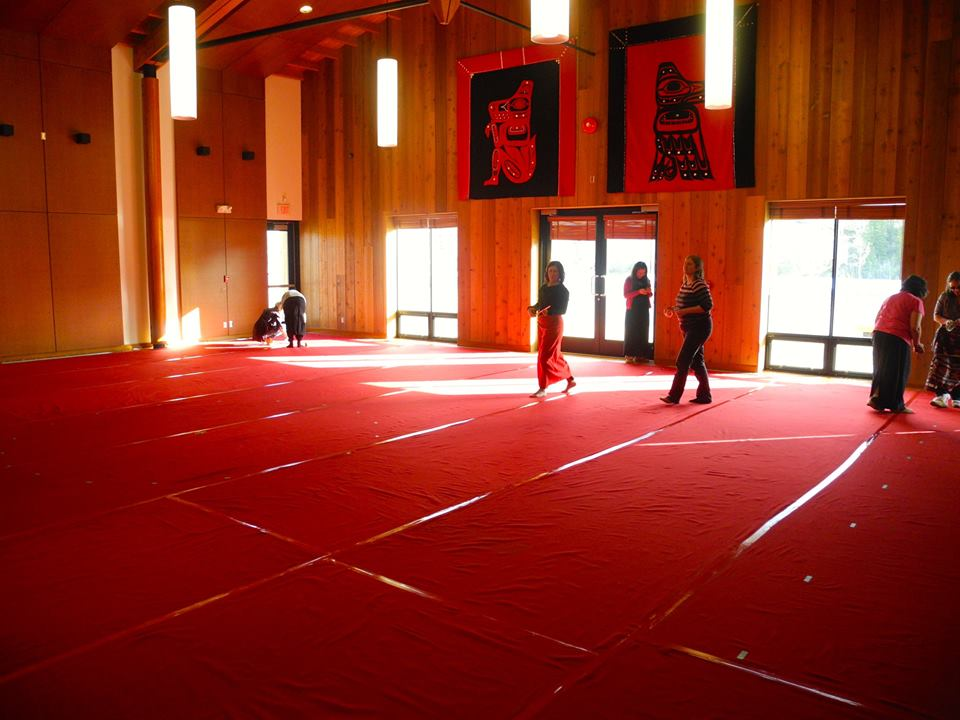 Auditorium with a few people walking on a floor covered entirely with red cloth