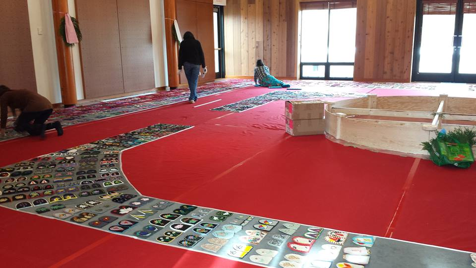 Floor with red cloth with paths of beaded and decorated moccasin tops laid out for many metres, people working on the paths