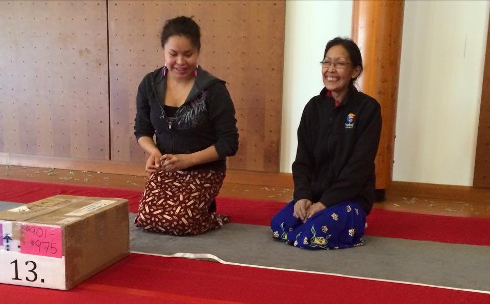 Younger woman and older woman in patterned skirts kneeling on fabric with box in front of them