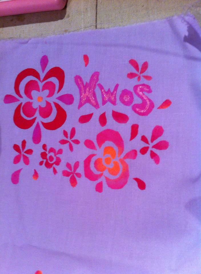 Fabric with painted flower stencils and the letters WWOS