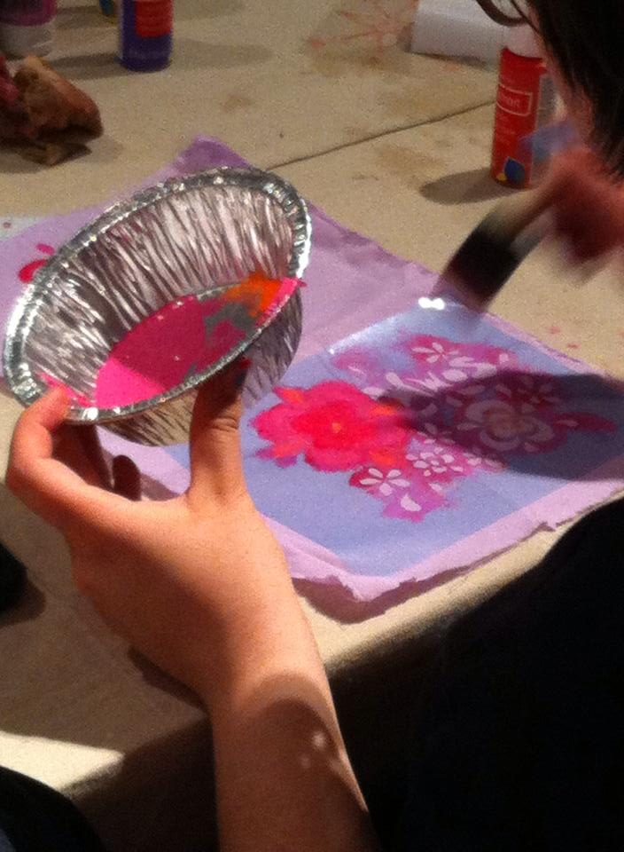 Person with tin foil pan of paint making a flower stencil on fabric