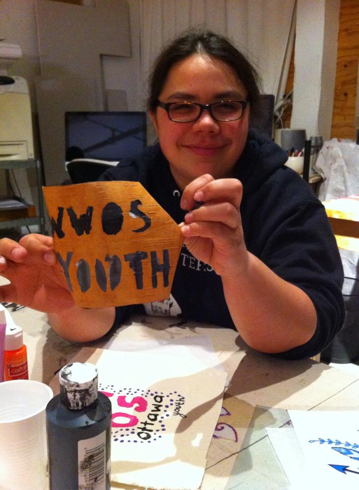 young woman in glasses holding up a piece of birch bark painted with the words WWOS Youth